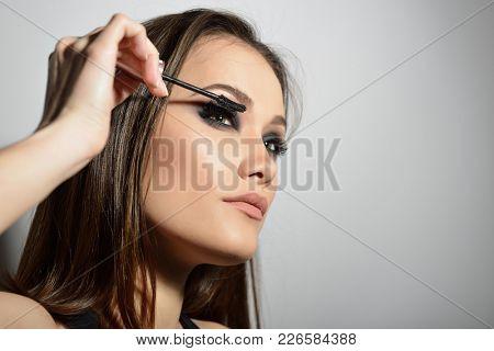 Young beautiful model applying makeup. Fashion girl with mascara. Eyelash makeup.