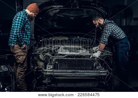 Two Mechanics Repairng A Car In A Garage.