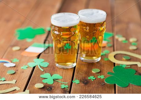 st patricks day, holidays and celebration concept - glasses of draft beer, shamrock and gold coins on wooden table