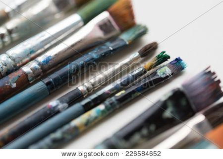 fine art, painting, creativity and artistic tools concept - close up of dirty paintbrushes