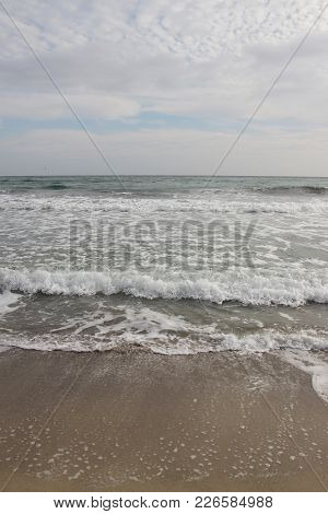 Cloudy Weather. Golden Sand, Waves And Foam. Cloudy Day On The Sandy Beach. Panoramic View Of Beauti