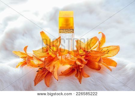 Bottle Of Perfume With Lily On White Fur Background