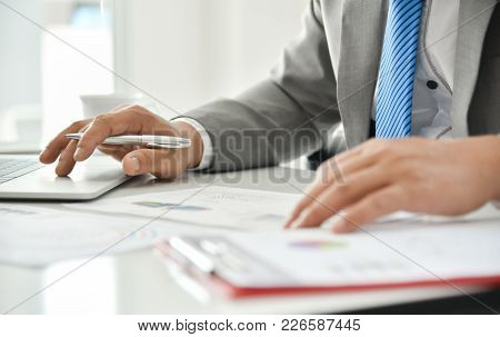 Businessman Hand Is Holding On Business Chart Or Graph Documents With A Pen. Man In Grey Suit And Bl