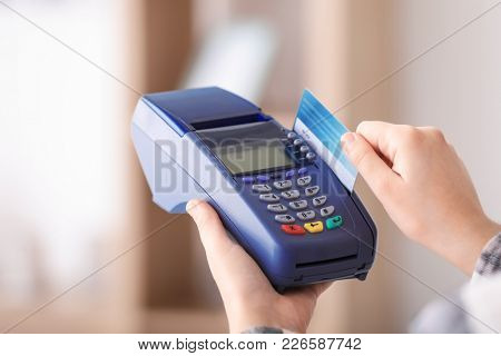 Woman using bank terminal for credit card payment indoors
