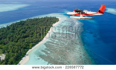 Seaplane flying above exotic iceland in Maldives. Exotic holiday in Indian ocean
