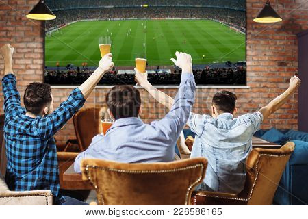 Group Of Young Men Cheering On Their Favorite Football Team Watching The Game On Tv At The Local Pub