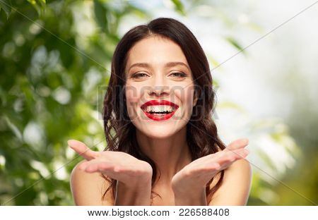 beauty, make up and people concept - happy smiling young woman with red lipstick holding something imaginary on palms over green natural background