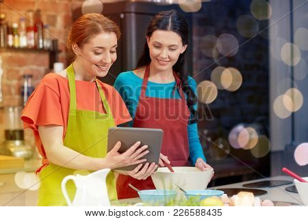cooking class, friendship, food, technology and people concept - happy women with tablet pc computer in kitchen