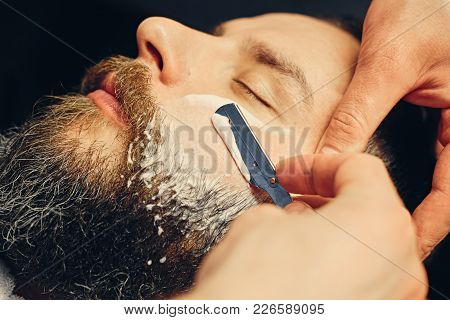 Close up portrait of barber shaving bearded male with a sharp razor in a saloon. poster