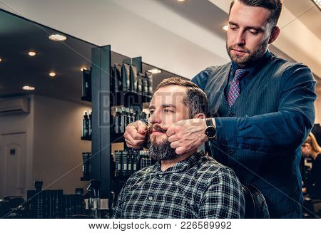 Stylish Male Hairdresser Doing Haircut To A Bearded Man In A Barbershop.