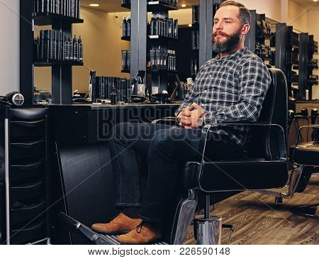 Portrait Of Bearded Male Dressed In A Fleece Shirt And Jeans Sits On A Chair In Hairdresser Saloon.