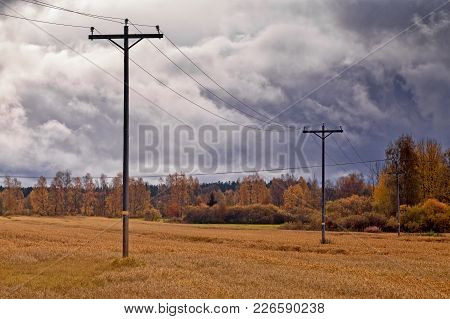 The Telephone Lines Stand On The Autumn Fields Under The Dramatic Skies In The Northern Finland. The
