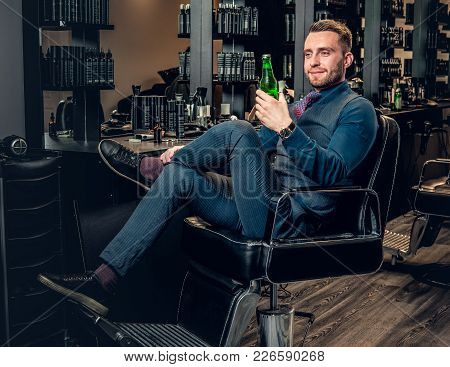 Portrait Of Stylish Male Sits On A Chair And Holds The Bottle With Beer In Hairdresser Saloon.