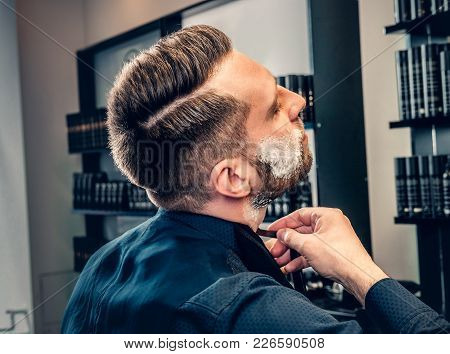 Stylish male shaving himself in a saloon. poster