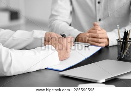 Male doctor filling up application form while consulting patient in clinic, closeup