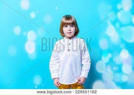 Ð¡ute six-year-old boy poses holding over blue background. Children's fashion. Studio shot.