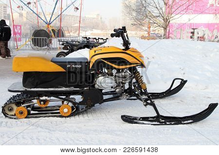Perm, Russia - February 10, 2018: Modern Yellow Snowmobile Stands Near The Ice Town On The Street Of
