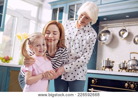 Happy Family. Pleasant Little Girl Standing In The Kitchen And Being Hugged By Her Mother And Grandm