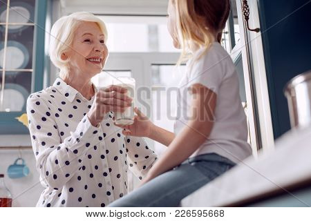 Healthy nutrition. Joyful elderly woman handing a glass of milk to her little granddaughter and smiling at her fondly while the girl sitting on the kitchen counter poster