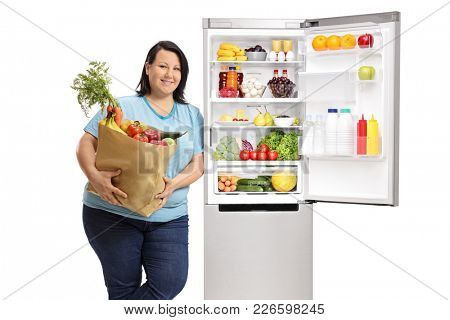 Overweight woman with a paper bag filled with fruit and vegetables leaning against an open fridge isolated on white background