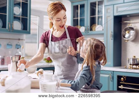 Great Job. Upbeat Young Woman In An Apron Looking At A Small Cookie In Her Daughters Hands With Exci