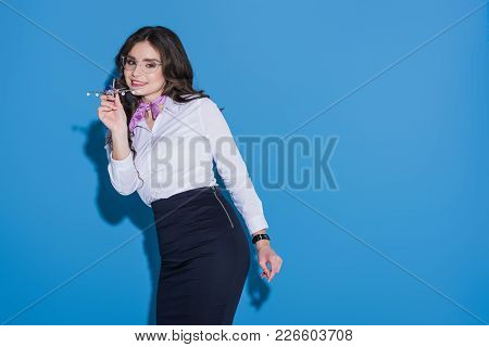 Attractive Stewardess With Plane Model On Blue