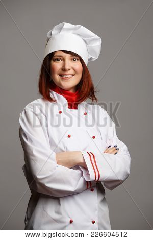 Photo of cook girl in white robe and cap with crossed hands
