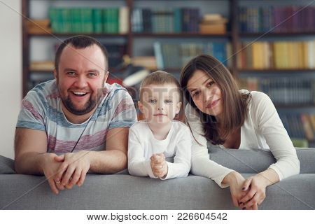 Photo of smiling parents with boys on gray sofa
