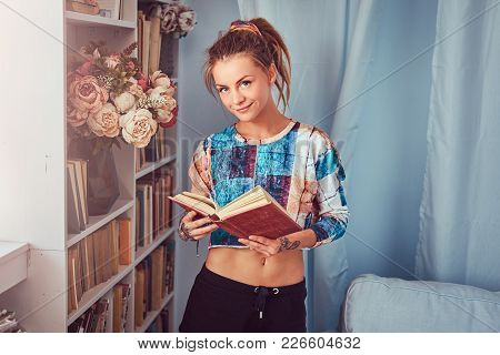 Young Tattooed Girl Standing Near A Bookcase Read A Book At Home.