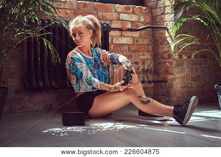 A Beauty Tattoed Girl In Casual Clothes Sits On The Floor And Plays Video Games In A Room With Loft