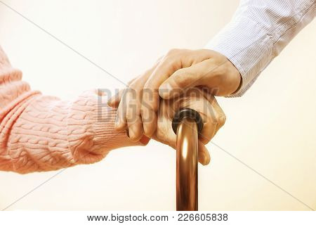 Mature Female In Elderly Care Facility Gets Help From Hospital Personnel Nurse. Close Up Of Aged Wri