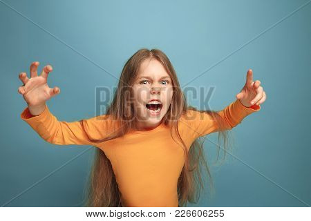 The Surprise, Rage. The Screaming Surprised Teen Girl On A Blue Studio Background. Facial Expression