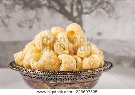 Antique Metal Bowl With Crunchy Pork Cracklings With Gray Background