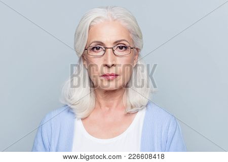 Close Up Portrait Of Serious, Aged, Charming Woman In Glasses Over Grey Background