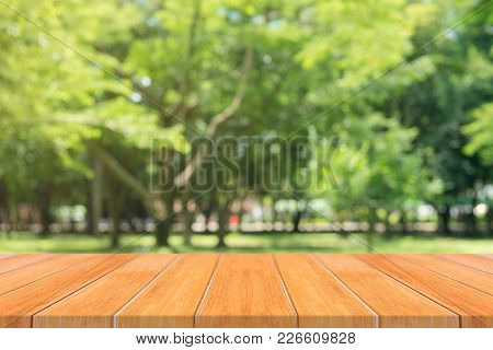 Wooden Board Empty Table In Front Of Blurred Background. Perspective Brown Wood Table Over Blur Tree