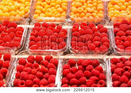 Assortment Of Fresh Rasberries On Display At A Produce Market