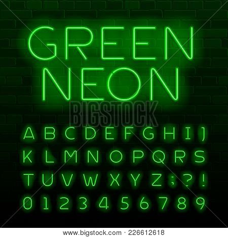 Green Neon Lamp Alphabet Font. Neon Color Shiny Letters, Numbers And Symbols. Brick Wall Background.