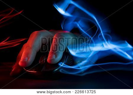 The Hand Lies On The Computer Mouse. Blue And Red Light Effect. Gamer.
