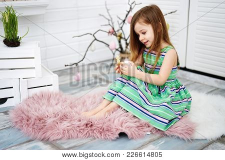 Four Years Old Girl Holding Pink Big Egg In Her Hands On White Background Around Easter Decorations