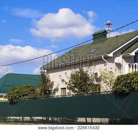 Asphalt Shingle. Decorative Bitumen Shingles On The Roof Of A Brick House. Fence Made Of Corrugated