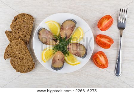 Plate With Slices Of Smoked Mackerel, Dill, Lemon, Pieces Of Bread, Tomato And Fork On Wooden Table.