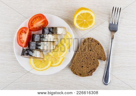 Plate With Slices Of Smoked Mackerel, Lemon, Tomato, Piece Of Bread And Fork On Wooden Table. Top Vi