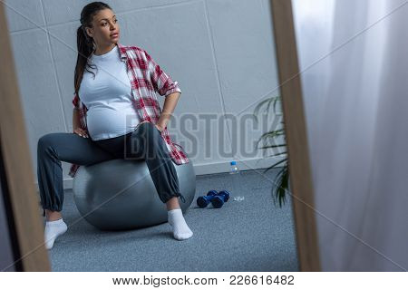 Mirror With Reflection Of African American Pregnant Woman Sitting On Fit Ball