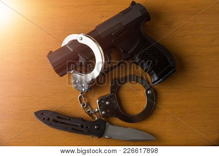 Tactical Gear Set Of Pistol Gun Knife Handcuff And Clock On Wooden Background. Police Or Military Eq