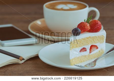 Homemade Delicious And Soft Strawberry Shortcake On Wood Table Beside Smartphone And Hot Cappuccino