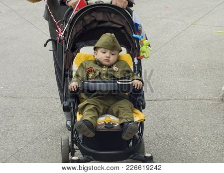 Pyatigorsk, Russia - May 09, 2017: A Little Boy In Uniform For The Day Of Victory In Baby Stroller.c