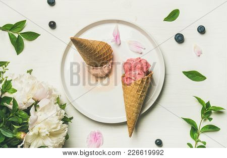 Flat-lay Of Pink Strawberry And Coconut Ice Cream Scoops, Sweet Cones And Peony Flowers Bouquet On P