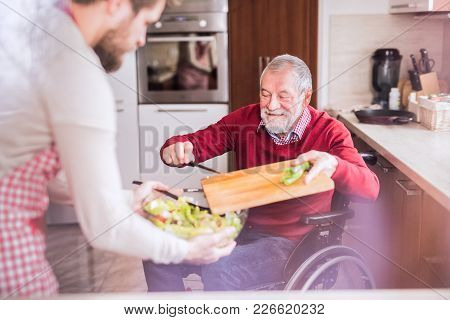 Young Son With His Senior Father In Wheelchair Cooking In The Kitchen. Two Generations Indoors. Shot