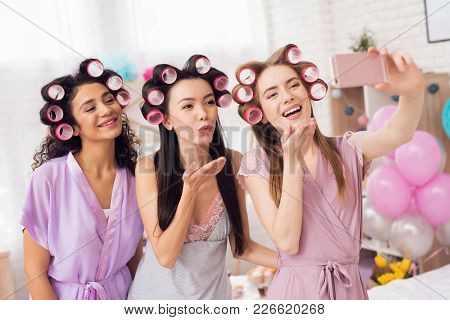 Three Girls With Curlers In Their Hair Taking Selfie. They Are Celebrating Women's Day March 8.