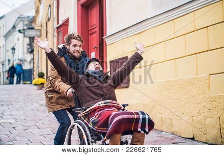 Father In Wheelchair And Young Son On A Walk, Having Fun. A Carer Assisting Disabled Senior Man.
